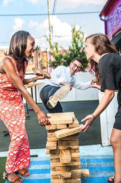CL interns Brittaney Major, Sean Billings and Deborah Swearingen hone their architectural skills on Jumbo Jenga at Blind Pig. - JUSTIN DRISCOLL