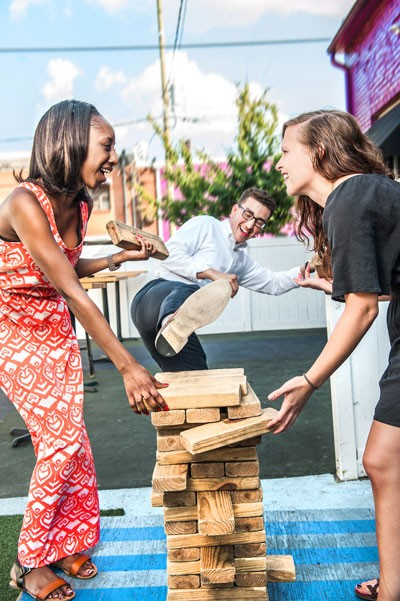 CL interns Brittaney Major, Sean Billings and Deborah Swearingen hone their architectural skills on Jumbo Jenga at Blind Pig. - JUSTIN DRISCOLL