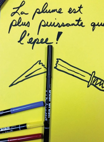 "Dink Nolen creates doodles to help promote the local craft beer scene — never anything risky or political. But he felt compelled to take a visual stand. ""The adage 'The pen is mightier than the sword' came to mind. So I quickly doodled a broken sword with those words in French, placed my pens with the doodle, snapped a picture, and tweeted it."" - COURTESY OF DINK NOLEN III"