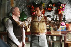 STEPHEN VAUGHAN / TOUCHSTONE - DRESSED TO THRILL Cutter (Michael Caine) helps fit Robert Angier (Hugh Jackman) with a special apparatus for his magic act in The Prestige.