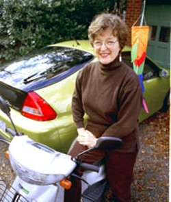 RADOK - Envionmental activist Nancy Bryant, who has urged - local government to join in a lawsuit against the EPA, - sits on her scooter, in front of her electric/gas hybrid - car.