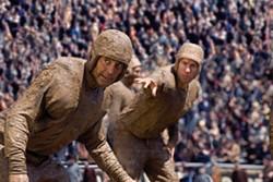 MELINDA SUE GORDON / UNIVERSAL - GRIDIRON GRIME: Dodge (George Clooney) and Carter (John Krasinski) get down and dirty in Leatherheads. This scene was filmed at Charlotte's Memorial Stadium.