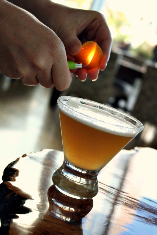 Light orange peel on fire and allow the orange oil to drip into the cocktail.