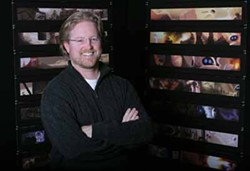 DEBORAH COLEMAN / DISNEY & PIXAR - MAKING HIS ROBOT FRIENDS: Director Andrew Stanton stands in front of images of WALL-E and EVE.
