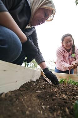 MEREDITH JONES - Muneeyd Aleas, left, with Maluz Bazquez planting in the garden.