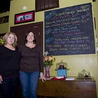 ON BOARD: Lori Pearson (left) and Lisa Burris next to the day's food offerings at Savor Café & Catering.