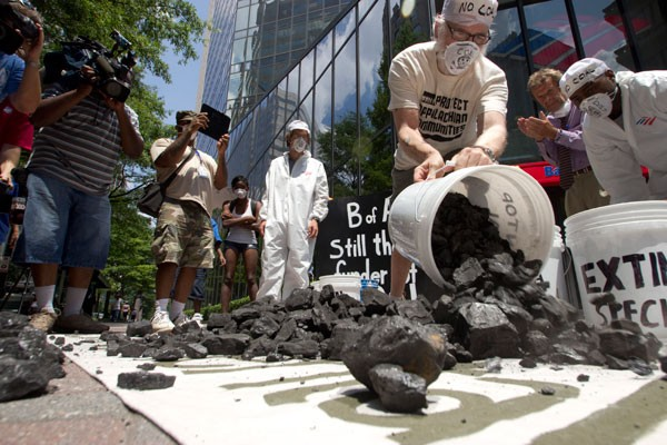 Photo captions: Activists dumped 500 pounds of coal in front of Bank Of America's headquarters during a street theatre protest Thursday to bring awareness to the bank's funding of the coal industry. - GRANT BALDWIN