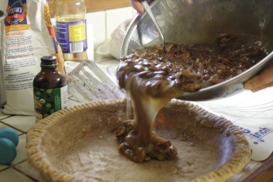 Pouring pecan pie filling into pan
