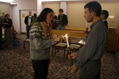 Sheila Stumph and Scott Bass lighting a candle at a prayer vigil for Willie Brown. - SCOTT LANGLEY