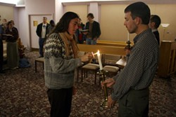 Sheila Stumph and Scott Bass lighting a candle at a prayer vigil for Willie Brown. - SCOTT LANGLEY