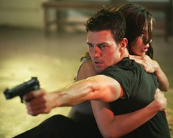 MARK FELLMAN / PARAMOUNT - SLUGS AND KISSES Ethan Hunt (Tom Cruise) takes aim while Julia (Michelle Monaghan) takes comfort in Mission: Impossible III