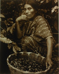 DISCOVERY PLACE - THE BIRTH OF COFFEE: A woman of Mayan descent from San Juan Atitlán, Guatemala, sits with her basket of coffee beans.