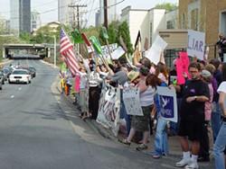 JARED NEUMARK - The Bush motorcade passes by Charlotte protestors.