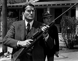 UNIVERSAL - TO KILL A RABID DOG: Atticus Finch (Gregory Peck, foreground) and Sheriff Heck Tate (Frank Overton) deal with a dangerous animal in To Kill a Mockingbird.