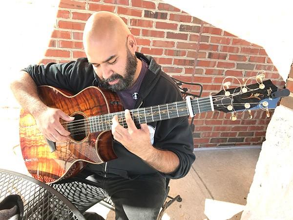 Banda sits at Mugs Coffee, picking the custom Taylor acoustic he named Ele.