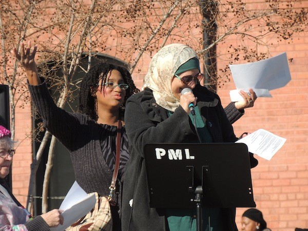 Rose Hamid speaks at First Ward Park, as Regina Grover cheers her on from behind. (Photo by Ryan Pitkin)