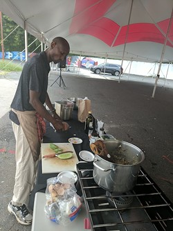 Njathi Kabui gets to work at a recent Sustainability Village market on West Trade Street. (Photo by Ryan Pitkin)