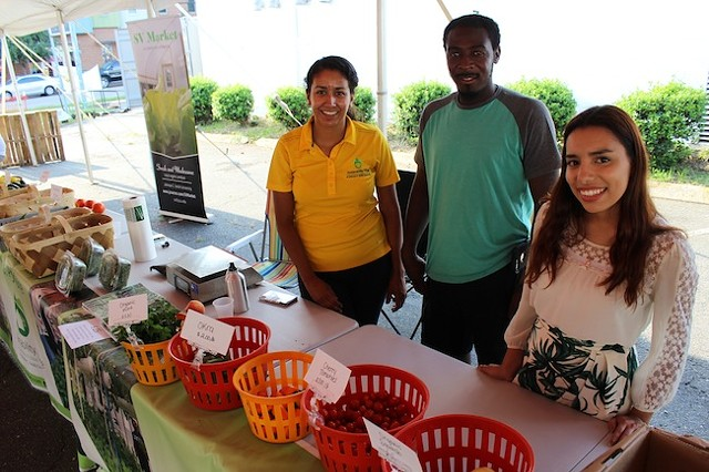 Brenda Montanez (right) with her fellow Sustainability Village volunteers at a recent Rosa Parks Farmer Market. (Photo by Ryan Pitkin)