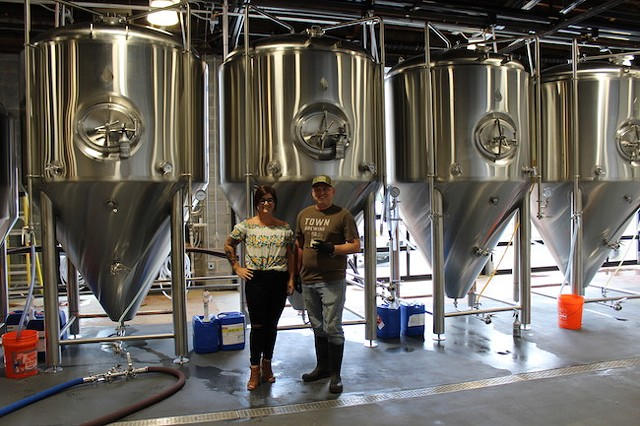 Heather Wendrow (left) and Brian Quinn in front of the tanks in the production room of Town Brewing. (Photo by Courtney Mihocik)