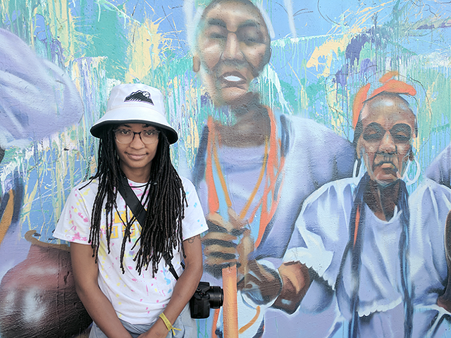 Janelle Dunlap in front of an unfinished part of the Manifest Future mural she's been helping with.