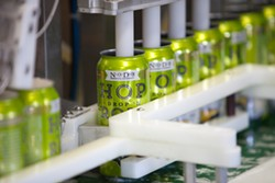 Cans of Hop DropN Roll come fresh off the canning line at Noda Brewing Company. (Photo by Jeff Hahne)