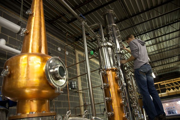 Andrew Porter, owner of Doc Porter's, adjusts valves during the distilling process. (Photo by Jeff Hahne)