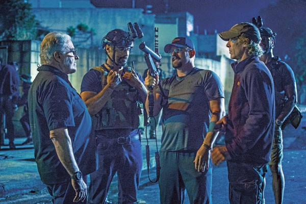 """John """"Tig"""" Tiegen (center) consults with cast and crew during the filming of 13 Hours. (Photo courtesy of Paramount Pictures)"""