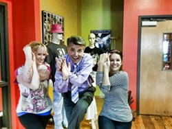 Larry Sprinkle learns a basic yoga move with some staff members while stopping by the CL offices in late 2014.