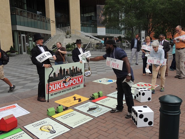"""A """"captive rate payer"""" hands money over to Duke Energy at Monday's """"Dukeopoly"""" game. - RYAN PITKIN"""