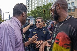 Capt. Mike Campagna engages with protesters outside of the Panthers game on Sunday, Sept. 25. - GRANT BALDWIN
