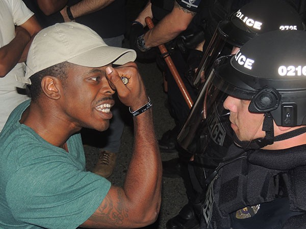 A protester shows a police officer his veteran's bracelet. - RYAN PITKIN