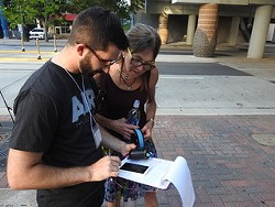 Cupini works with a volunteer in Uptown to measure air quality.
