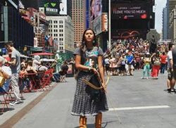 Apache Stronghold youth leader Naelyn Pike, Nosie's granddaughter, stands in Times Square while touring to raise awareness about the fight for Oak Flat. - STANDING FOX