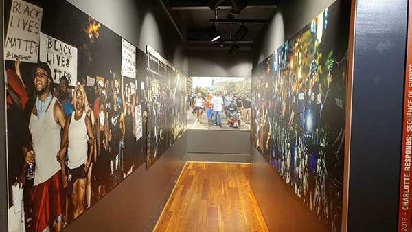A tunnel lined with life-size photos from the Charlotte Uprising also plays audio of the protests from above. - COURTESY OF LEVINE MUSEUM.