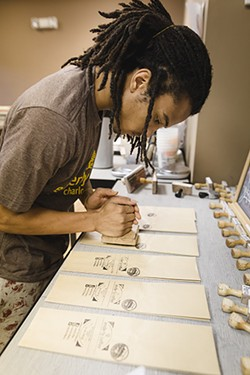 Pettiford hand-stamps individual Enderly Coffee bags. - PHOTO BY UNCLE JUT.