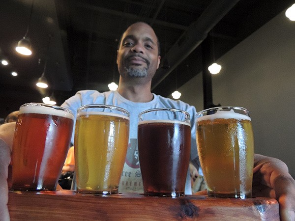 Tabu Terrell with a flight of beers. Photo by Ryan Pitkin.