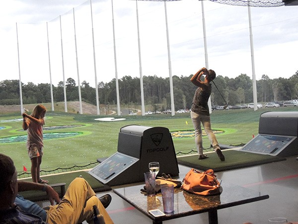 PGA Vice President Suzy Whaley (right) swings away at a recent PGA event at Topgolf Charlotte. In 2003, Whaley became the first woman since Babe Zaharias in 1945 to qualify for an event on the PGA Tour. The little one taking a cut next to Whaley has the potential to surpass her, we think. (Photo by Ryan Pitkin)