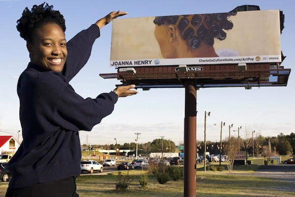 Rock Hill artists and ArtPop alum Joanna Henry poses with her billboard in York County, South Carolina.