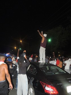 "Jamil ""King Millz"" Gill stands atop a car he was driving to capture the protests on a live stream on Sept. 20."
