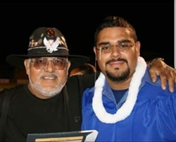 Banda's proud father (left) beams on his son's high school graduation day in 2005.