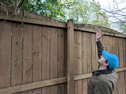Kevin Jones points to where a proposed development could tower over his property line. (Photo by Ryan Pitkin)