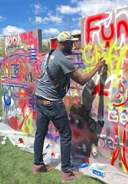 Crenshaw paints on trash.