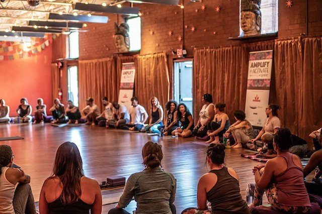 Simthong (black shirt, background), shares her story with attendees of the recent Yoga One event. (Photo by Grace Borchers/SweatNet CLT)