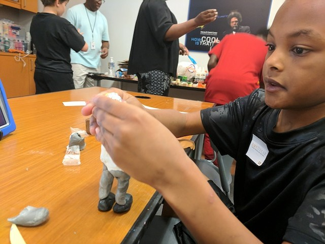 Kaison Ingram, 9, builds a clay model at the recent workshop. (photo by Ryan Pitkin)
