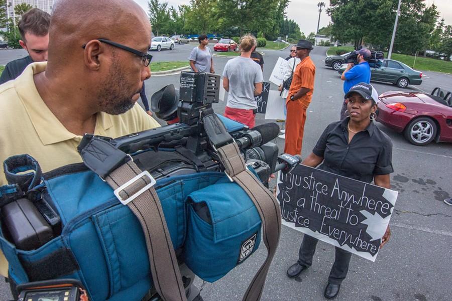 Activist Kassandra Ottley speaks to a television news camera.