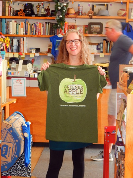 Lee Rathers, owner of The Greener Apple, showing off some gear from the food shop within a store.