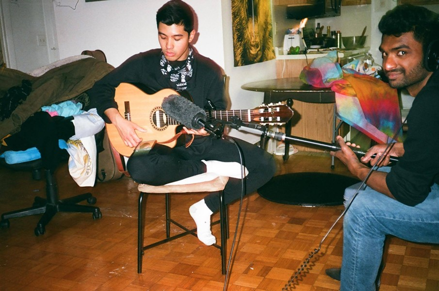 Quisol strums an acoustic guitar at Hermit Mo Studios in December. (Photo by Mo Kwok)