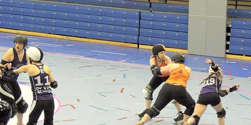 Charlotte Roller Girls Season Opener Ka$h Honey (right) zips past some blockers for a point-scoring move. Ryan Pitkin