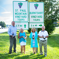 (L-R) Alan Ward and Barbara Ward of Saint Paul Mountain Vineyards and Sandra Oates and Lemuel Oates of Burntshirt Vineyards stand under their respective signs