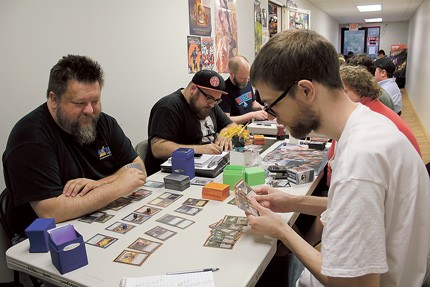 (From left) John Hartness, Jake Strunin and Owen Tavener play Magic: The Gathering at Rebel Base during a Monday night event. - KAILA BURTCH
